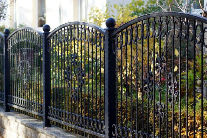 Żelazne ogrodzenie pomalowane na czarno, osadzone na kamiennej podmurówce.