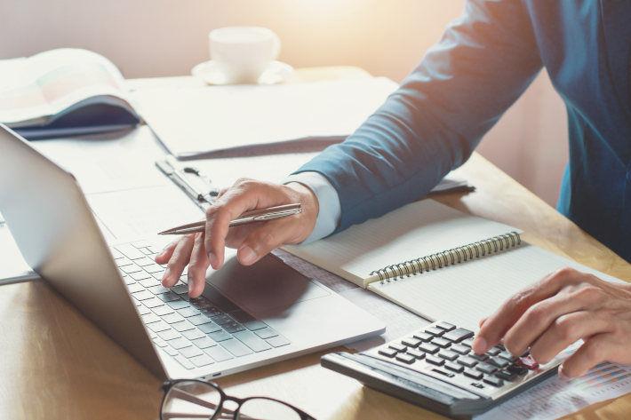 Mężczyzna korzystający z laptopa i dokonujący obliczeń na kalkulatorze