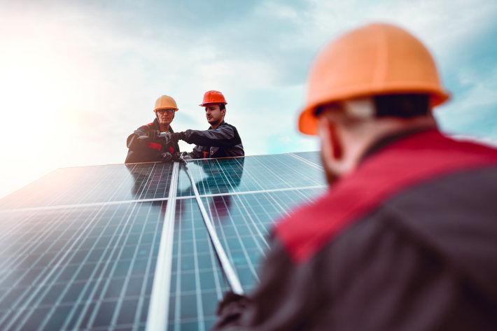 Robotnicy montujący panele fotowoltaiczne