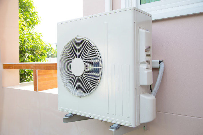 Biała pompa ciepła na ścianie
