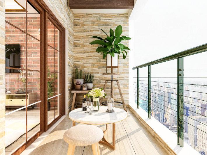 Nowoczesny, słoneczny balkon w bloku mieszkalnym z drewnianą podłogą oraz elewacją z kamiennej klinkierówki