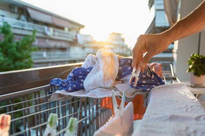 Ręka osoby rozwieszającej pranie na sznurkach, rozciągniętych na balkonie w bloku mieszkalnym