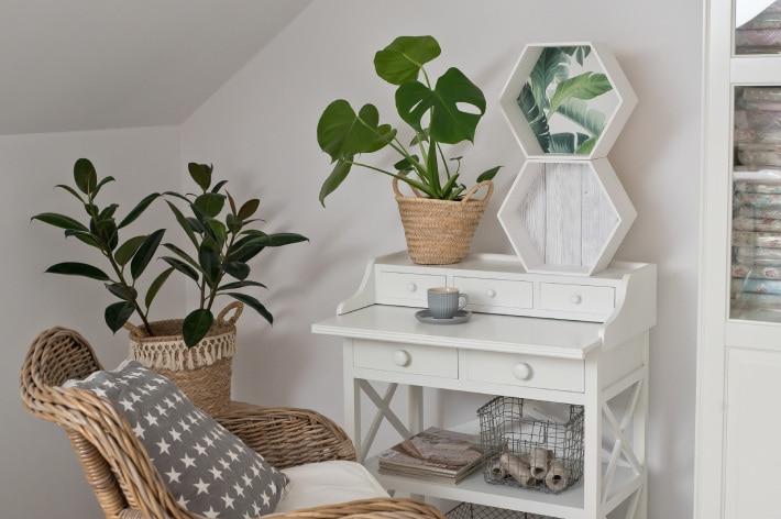 Biały salon w stylu skandynawskim z białymi pólkami sześciokątnymi stojącymi na białym biurku