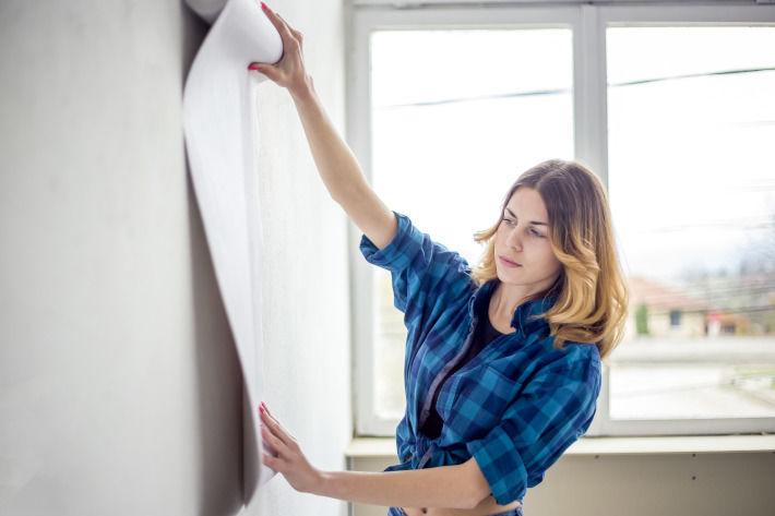 Kobieta kładzie tapetę w pokoju
