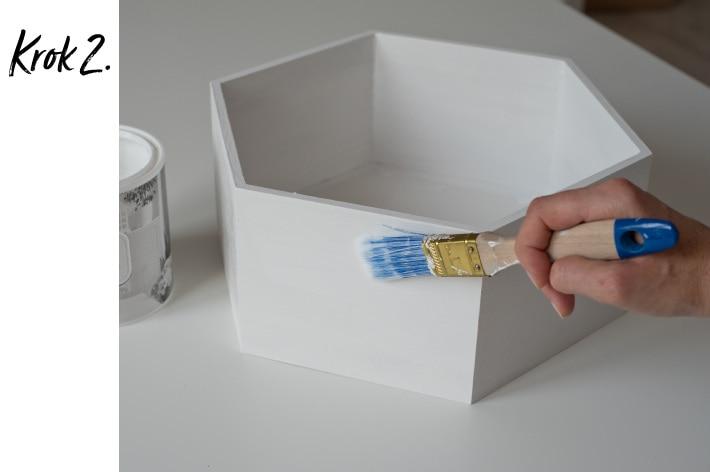Malowanie białej półki sześciokątnej bezbarwnym lakierem za pomocą pędzla